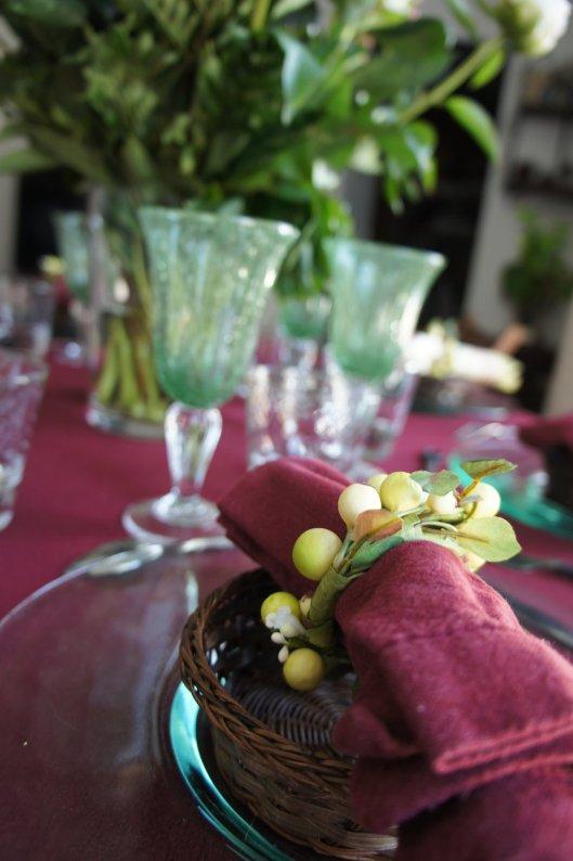 Verres bullés vert d'eau, assiettes en verre, serviettes entourées de ronds végétaux...