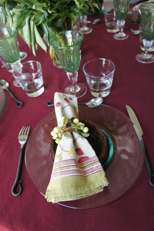 ...couverts en fer forgé ou serviettes vertes et fleuries composent cette table...
