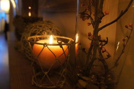 Des bougies mauve pâle sont allumés, les branches de prunus sont emprisonnées dans un vase en verre...