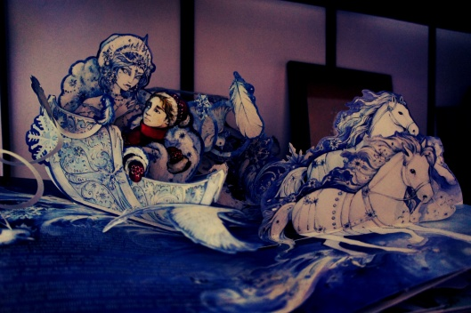 """Posé sur une étagère, un livre en relief du conte de """"La Reine des Neiges"""" par Andersen..."""