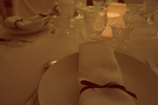 Des serviettes brodées chinées dans une brocante sont ceintes d'un ruban de satin noir, seul couleur forte de la table.