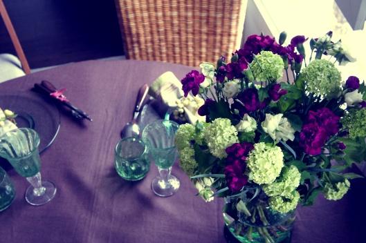 Sur la table, un beau bouquet d'œillets prune et de fleurs vertes...